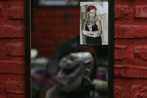 An earlier photograph of Maria Jose Cristerna is seen as she is reflected in a mirror in her tattoo parlour and boutique in Guadalajara