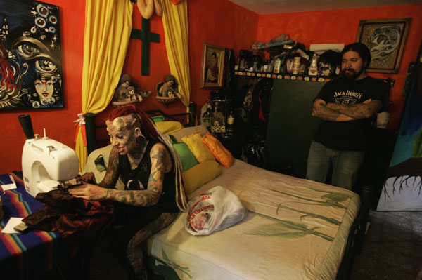 Maria Jose Cristerna, 36, a mother of four, tattoo artist and former lawyer, works at her sewing machine while chatting with her partner David Pena at their home in Guadalajara