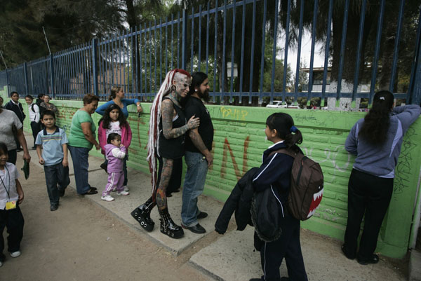 Maria Jose Cristerna, 36, a mother of four, tattoo artist and former lawyer, greets a girl while waiting with her partner David Pena for her children outside a school in Guadalajara