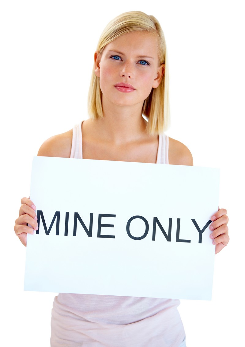 Studio shot of a beautiful young woman holding up a sign reading 'MINE ONLY'