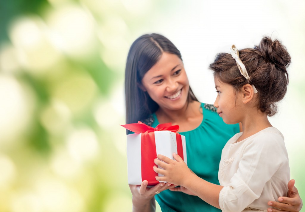 holidays, presents, christmas, family, child and x-mas, birthday concept - happy mother and child girl with gift